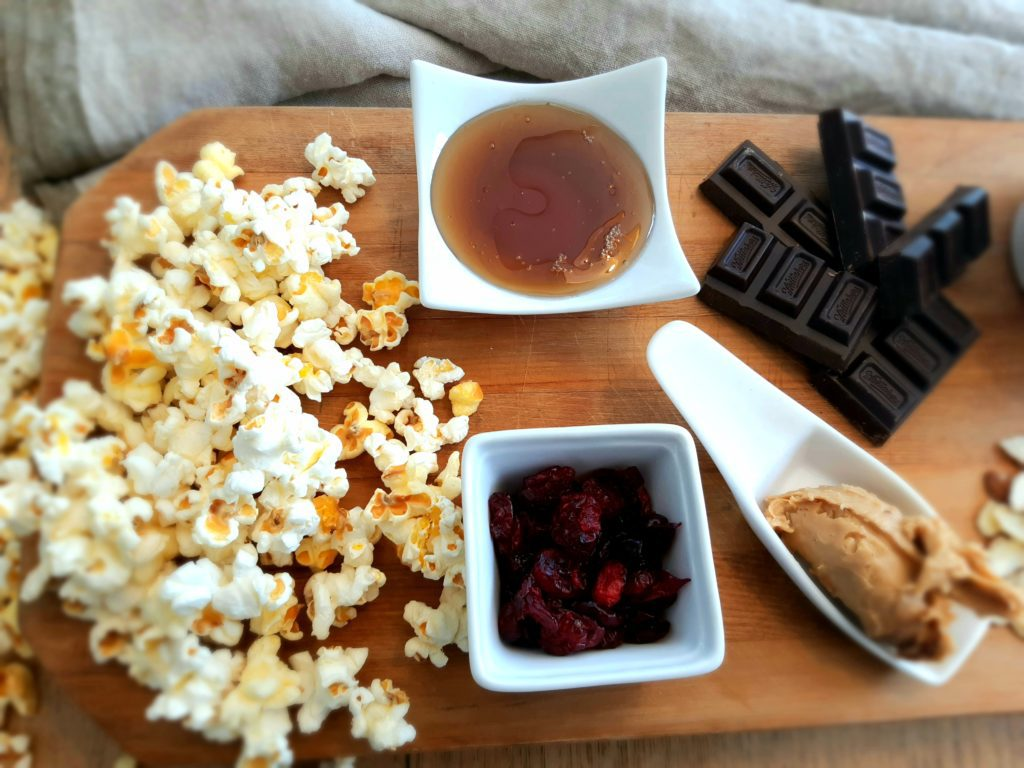 Popcorn, maple syrup, cranberries, dark chocolate, nut butter, oil, almonds on a chopping board